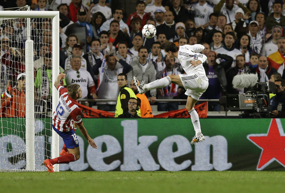 Photo - Real's Gareth Bale, right,  scores his side's 2nd goal, during the Champions League final soccer match between Atletico Madrid and Real Madrid in Lisbon, Portugal, Saturday, May 24, 2014. (AP Photo/Francisco Seco)