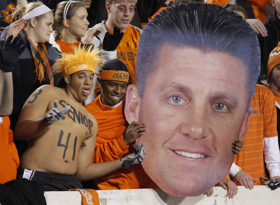 Photo - Cowboy fans have fun in the stands with a giant Mike Gundy cutout during the Bedlam college football game between the University of Oklahoma Sooners (OU) and the Oklahoma State University Cowboys (OSU) at Boone Pickens Stadium in Stillwater, Okla., Saturday, Nov. 27, 2010. Photo by Chris Landsberger, The Oklahoman