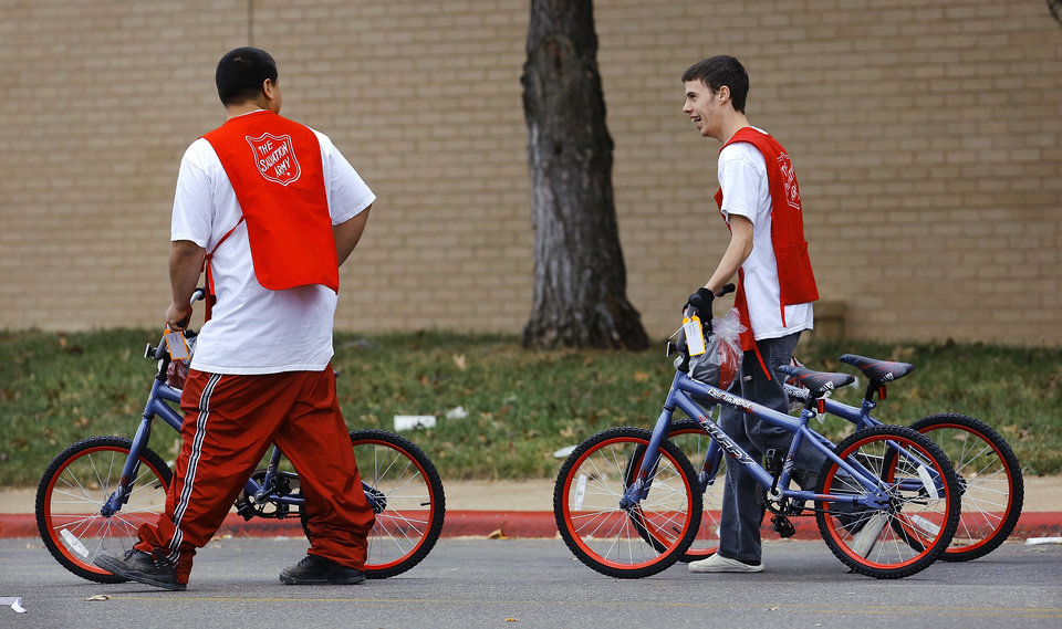 Volunteers walk three bicycles to a waiting vehicle during The  Salvation Army and Feed The Children distribution event.