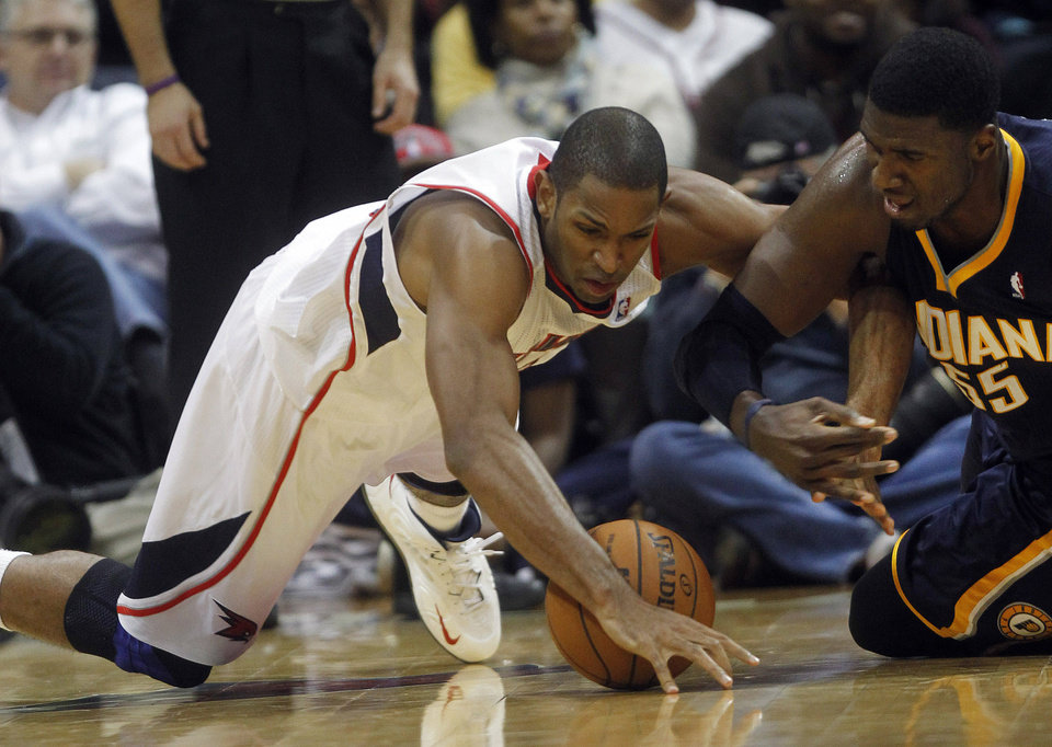 Atlanta Hawks power forward Al Horford, left, and Indiana Pacers center Roy Hibbert (55) dive for a loose ball in the first half of an NBA basketball game on Wednesday, Nov. 7, 2012, in Atlanta. (AP Photo/John Bazemore)