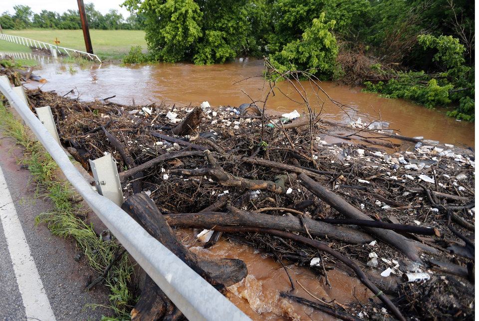 Photo - Debris washed against the guard rail on Franklin road on Saturday, June 1, 2013 in Norman, Okla.  illustrates the level of flood water damage after Friday night's storm  Photo by Steve Sisney, The Oklahoman