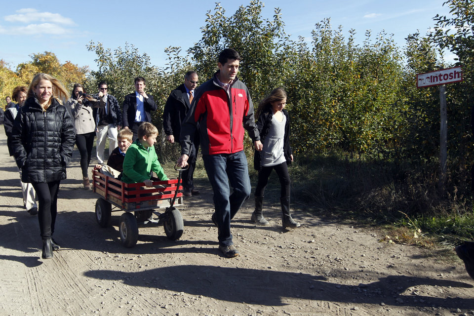 Photo -   Janna Ryan, right, walks alongside her husband Republican vice presidential candidate, Rep. Paul Ryan, center, R-Wis., as he pulls his sons Charlie, front, and Sam in a wagon holding his daughter Liza's hand on their way to the pumpkin patch at the Apple Holler farm, Sunday, Oct. 7, 2012 in Sturtevant, Wis. (AP Photo/Mary Altaffer)