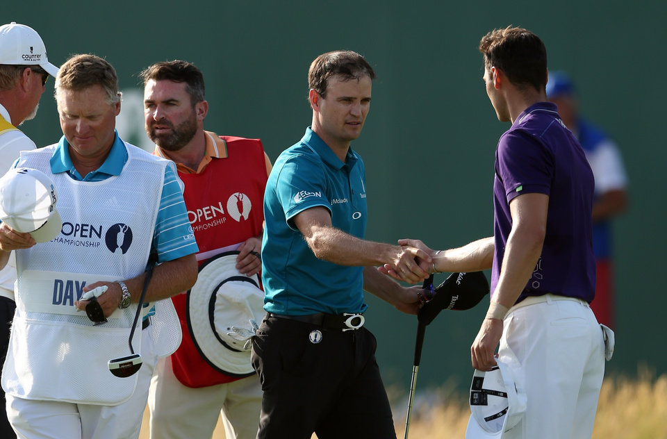 Photo - Zach Johnson of the US and Martin Kaymer of Germany shake hands on the 18th green at the end of their round on the first day of the British Open Golf championship at the Royal Liverpool golf club, Hoylake, England, Thursday July 17, 2014. (AP Photo/Jon Super)