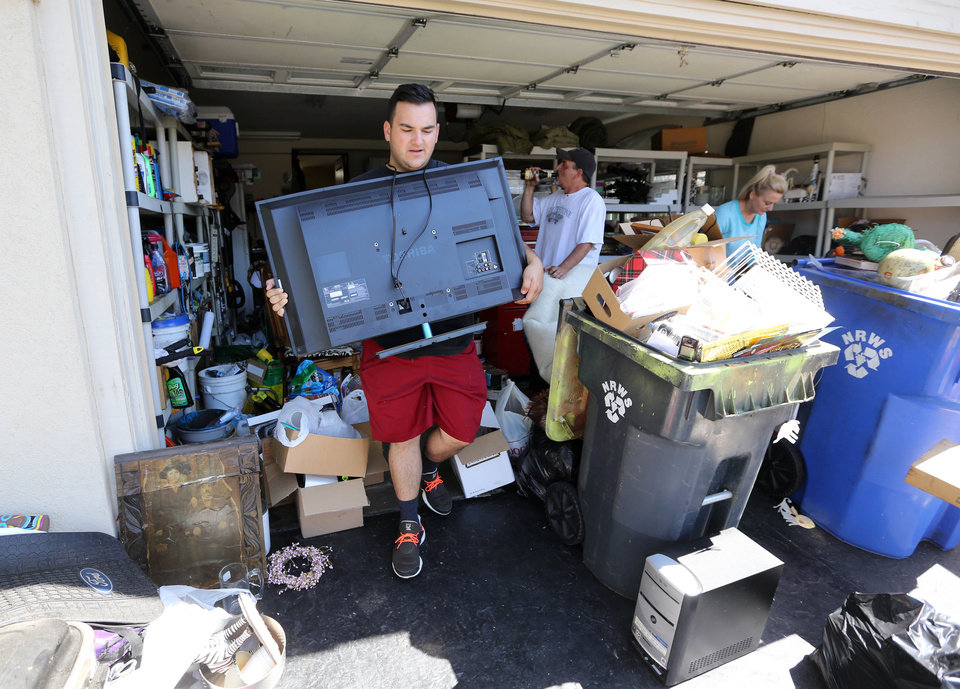 Photo - Derek Antti carries a television from his grandparents' home after an early morning earthquake   Sunday, Aug. 24, 2014, in Napa, Calif.  The largest earthquake to hit the San Francisco Bay Area in 25 years struck before dawn on Sunday. (AP Photo/Rich Pedroncelli)