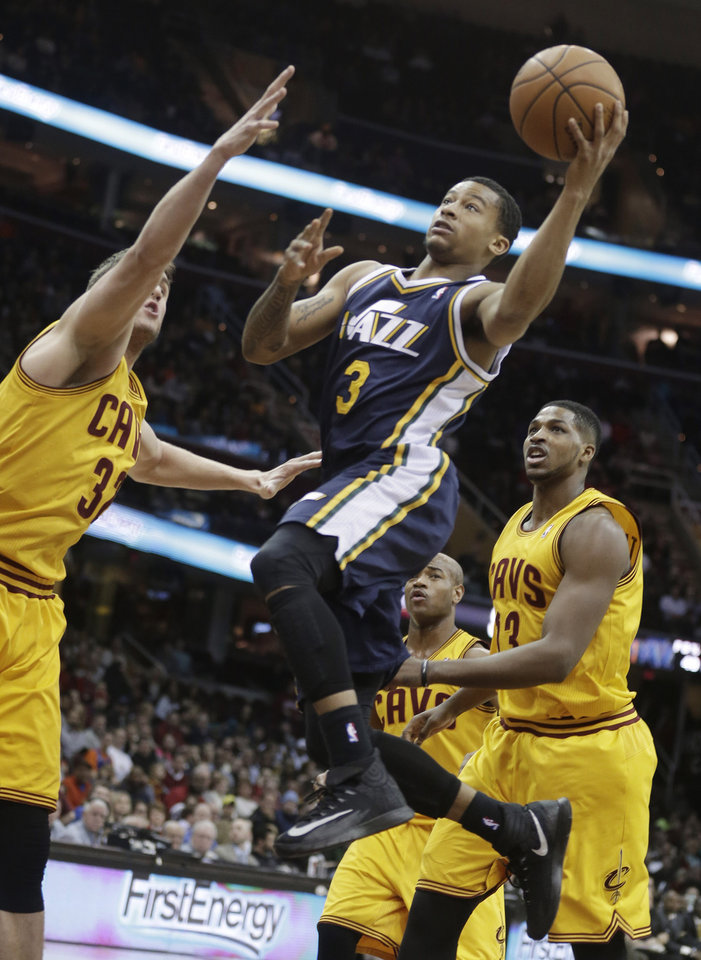 Photo - Utah Jazz's Trey Burke, center, shoots past Cleveland Cavaliers' Spencer Hawes, left, and Tristan Thompson (13), from Canada, during the first quarter of an NBA basketball game on Friday, Feb. 28, 2014, in Cleveland. (AP Photo/Tony Dejak)