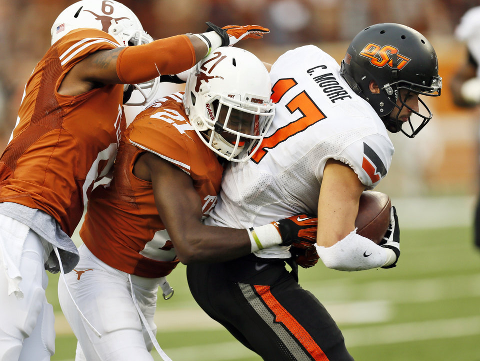 UT's Quandre Diggs (6) and Duke Thomas (21) stop Oklahoma State's Charlie Moore (17) after a catch during a college football game between the Oklahoma State University Cowboys (OSU) and the University of Texas Longhorns (UT) at Darrell K Royal - Texas Memorial Stadium in Austin, Texas, Saturday, Nov. 16, 2013. OSU won, 38-13. Photo by Nate Billings, The Oklahoman
