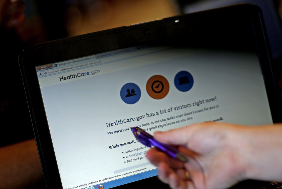 Photo - Elizabeth Rich points to a web page for the Affordable Care Act as she helps people sign up for health insurance at Swope Health Services Monday, March 31, 2014, in Kansas City, Mo. Today is the deadline to sign up for an Affordable Health Care insurance plan however, people who begin the enrollment process but aren't able to complete it by 11:59 p.m. because of a system issue may qualify for a special provision that will allow them to enroll after Monday night. (AP Photo/Charlie Riedel)