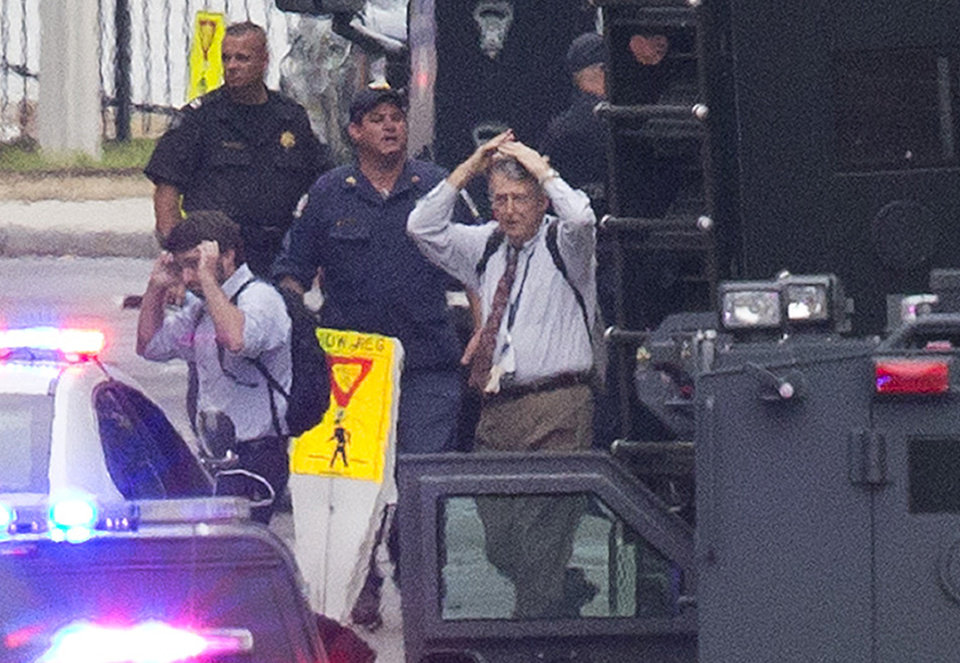 Photo - People hold their hands to their heads as they are escorted out of the building where a deadly shooting rampage occurred at the Washington Navy Yard in Washington, Monday, Sept. 16, 2013. One shooter was killed, but police said they were looking for two other possible gunmen wearing military-style uniforms. (AP Photo/Jacquelyn Martin)