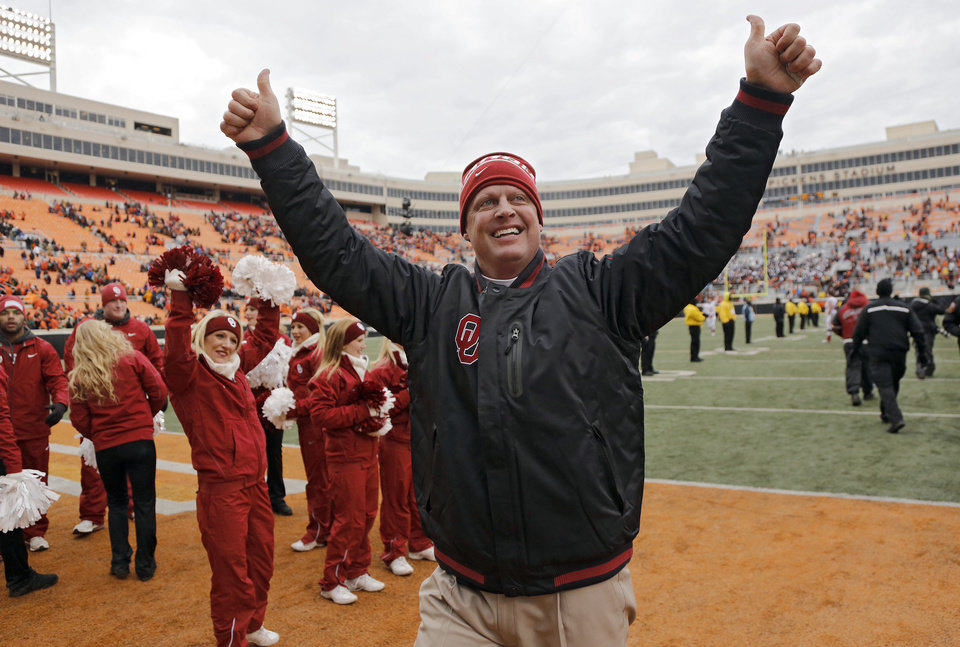 Photo - Assistant coach Cale Gundy celebrates after the Bedlam college football game between the Oklahoma State University Cowboys (OSU) and the University of Oklahoma Sooners (OU) at Boone Pickens Stadium in Stillwater, Okla., Saturday, Dec. 7, 2013. Photo by Chris Landsberger, The Oklahoman
