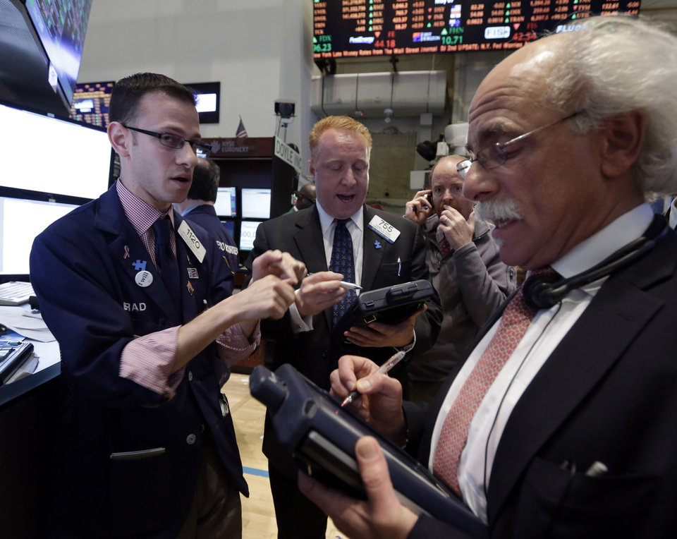 Photo - Specialist Bradley Kessler, lewft, works with traders on the floor of the New York Stock Exchange Tuesday, May 7, 2013.  The Dow Jones industrial average punched through another milestone Tuesday: its first close above 15,000. (AP Photo/Richard Drew)