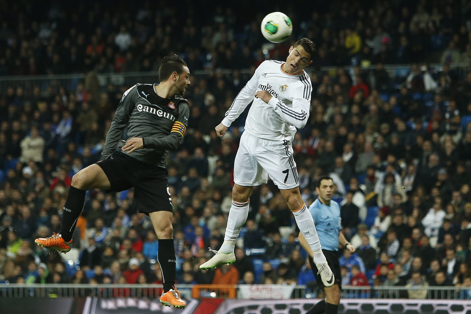 Photo - Real Madrid's Cristiano Ronaldol, right, in action with Espanyol's Sergio Garcia, left, during a Copa del Rey soccer match between Real Madrid and Espanyol at the Santiago Bernabeu stadium in Madrid, Spain, Tuesday, Jan. 28, 2014. (AP Photo/Andres Kudacki)