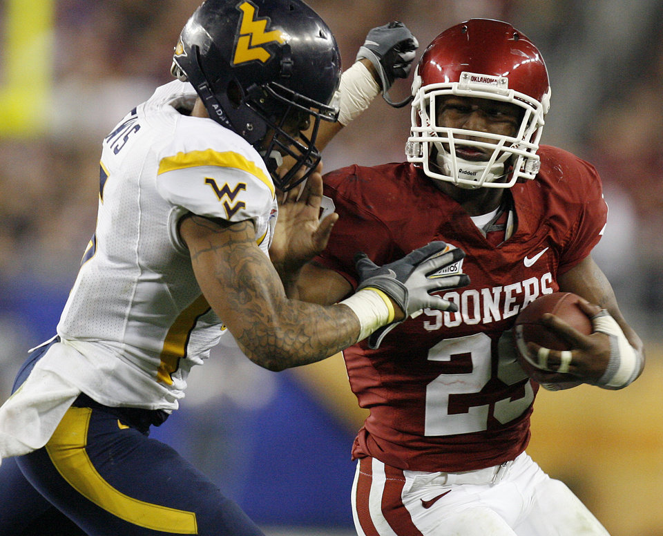 Photo - Chris Brown (29) tires to get past West Virginia's Antonio Lewis (6) during the second half of the Fiesta Bowl college football game between the University of Oklahoma Sooners (OU) and the West Virginia University Mountaineers (WVU) at The University of Phoenix Stadium on Wednesday, Jan. 2, 2008, in Glendale, Ariz. 