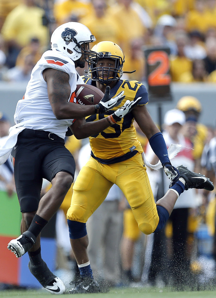 Oklahoma State's Tracy Moore (87) makes a catch in front of West Virginia's Darwin Cook (25) during the second half of a college football game between the Oklahoma State University and West Virginia University on Mountaineer Field at Milan Puskar Stadium in Morgantown, W. Va.,   Saturday, Sept. 28, 2013. Photo by Sarah Phipps, The Oklahoman