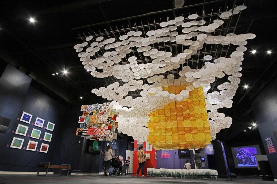 "Photo - Visitors look at Jacob Hashimoto's ""The Other Sun,"" a Minecraft-inspired installation made from 2,000 bamboo-and-paper kites, Friday, November 22, 2019, at Science Museum Oklahoma. The installation is the centerpiece of the museum's exhibit ""Cosmic Culture: Intersections of Art and Outer Space,"" [Photo by Doug Hoke/The Oklahoman]"