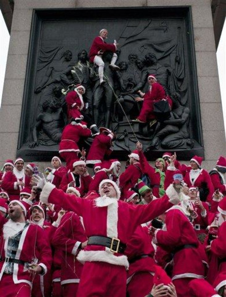 FILE - This Dec. 11, 2010 file photo shows people dressed in Santa Claus outfits at Trafalgar Square in London as part of the annual Santacon. SantaCon is coming to town _ in fact, to nearly 300 towns and cities around the world. Dozens, sometimes hundreds of red-suited revelers gather, barhop, stop traffic and pose for photos.  (AP Photo/Sang Tan, file)