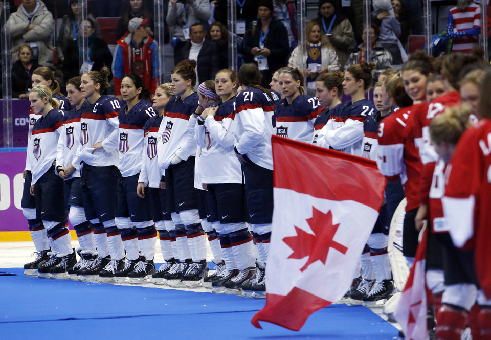 Photo - Team USA awaits their silver medals after losing 3-2 in overtime to Canada in the women's gold medal ice hockey game at the 2014 Winter Olympics, Friday, Feb. 21, 2014, in Sochi, Russia. (AP Photo/Mark Humphrey)