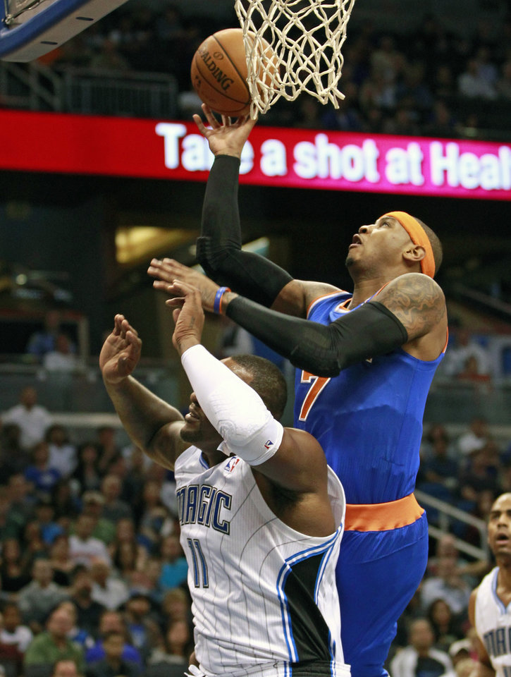 New York Knicks' Carmelo Anthony, right, goes over Orlando Magic's Glen Davis for a shot during the first half of an NBA basketball game, Tuesday, Nov. 13, 2012, in Orlando, Fla. (AP Photo/John Raoux)