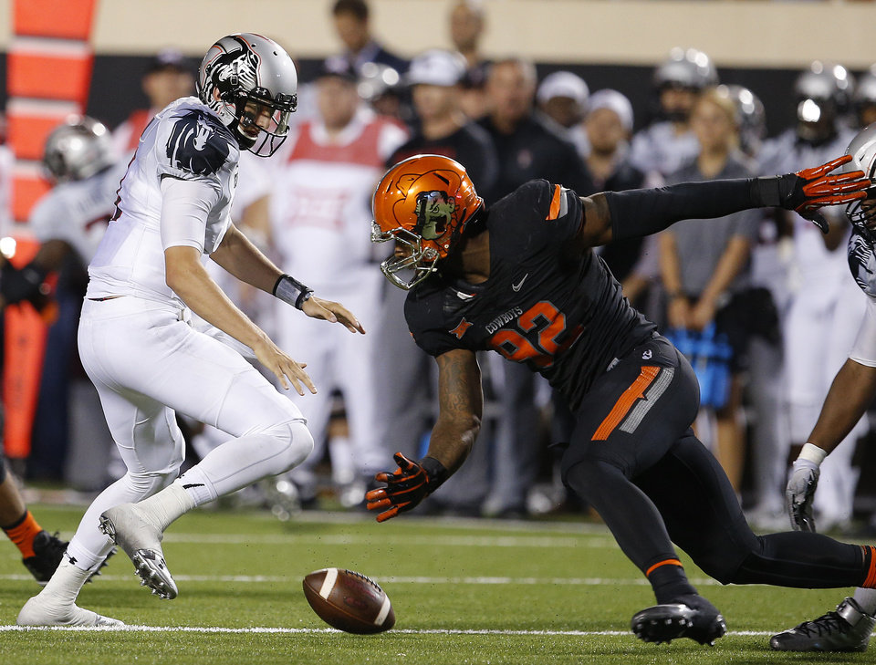 Photo - Oklahoma State's Jimmy Bean (92) knocks the ball away from Texas Tech's Davis Webb (7) during a college football game between the Oklahoma State Cowboys (OSU) and the Texas Tech Red Raiders at Boone Pickens Stadium in Stillwater, Okla., Thursday, Sept. 25, 2014. Photo by Bryan Terry, The Oklahoman