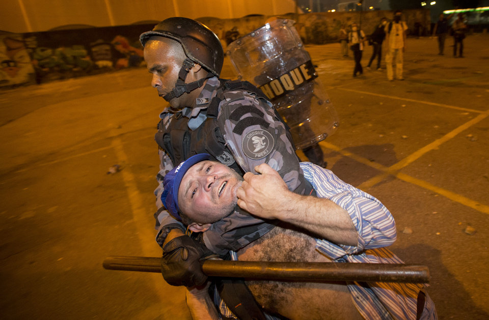 Photo - Military police detain a man during an anti-government protest in Rio de Janeiro, Brazil, Thursday, June 20, 2013. More than half a million Brazilians poured into the streets of at least 80 Brazilian cities Thursday in demonstrations that saw violent clashes and renewed calls for an end to government corruption and demands for better public services. Riot police battled protesters in at least five cities, with some of the most intense clashes happening in Rio de Janeiro, where an estimated 300,000 demonstrators swarmed into the seaside city's central area. (AP Photo/Victor R. Caivano)