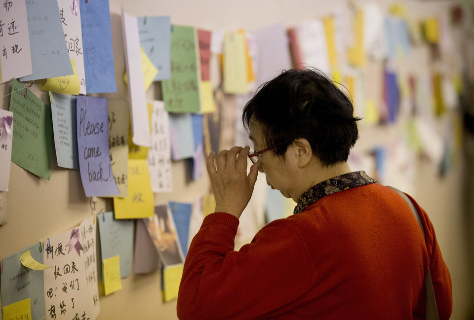 Photo - A woman, one of the relatives of Chinese passengers aboard the missing Malaysia Airlines flight MH370, looks at messages of wish for the passengers, at a hotel in Beijing, China Tuesday, April 1, 2014. Although it has been slow, difficult and frustrating so far, the search for the missing Malaysia Airlines jet is nowhere near the point of being scaled back, Australia's Prime Minister Tony Abbott said. The three-week hunt for Flight 370 has turned up no sign of the Boeing 777, which vanished March 8 with 239 people bound for Beijing from Kuala Lumpur. (AP Photo/Andy Wong)