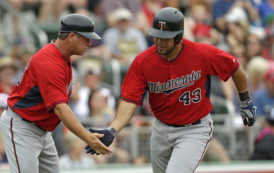 Photo - Minnesota Twins' Josmil Pinto (43) is greeted by third base coach Joe Vavra after hitting a home run during the seventh inning of an exhibition baseball game against the Boston Red Sox in Fort Myers, Fla., Saturday, March 29, 2014. The Twins won 7-4. (AP Photo/Gerald Herbert)