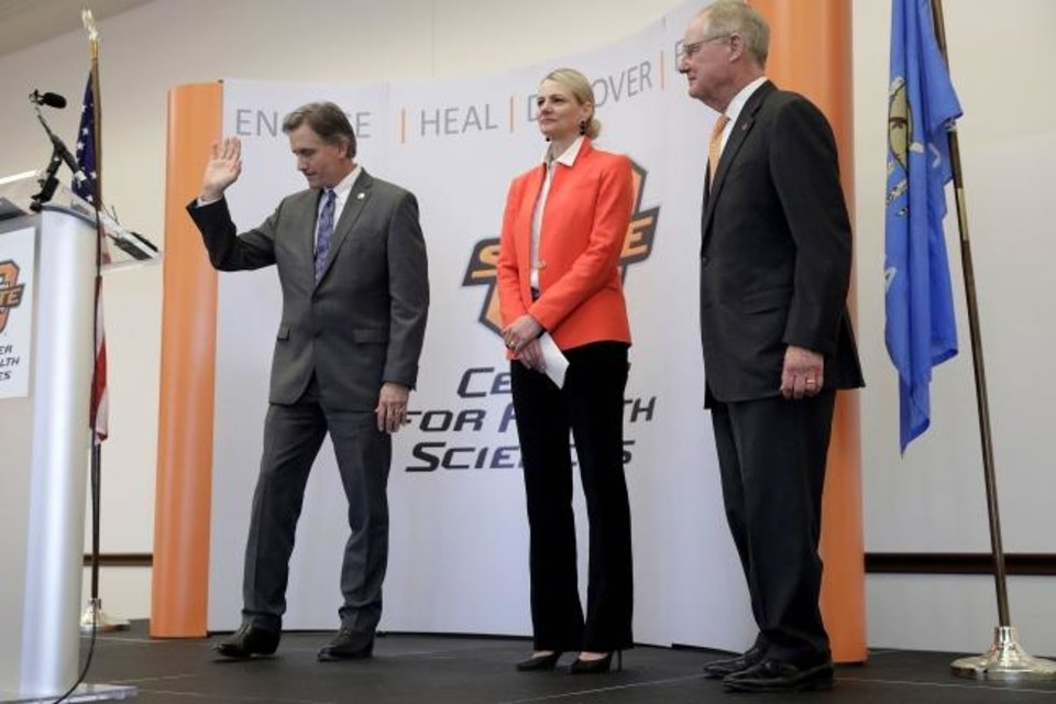 Photo -  Oklahoma Attorney General Mike Hunter acknowledges the crowd after speaking about a settlement with Purdue Pharma for opioid abuse, as Oklahoma State University Center for Health Sciences President Dr. Kayse Shrum and OSU President Burns Hargis, right, listen, Tuesday, March 26, 2019.  Purdue Pharma, the maker of OxyContin and the company's controlling family agreed Tuesday to pay a groundbreaking $270 million to Oklahoma to settle allegations they helped create the nation's deadly opioid crisis with their aggressive marketing of the powerful painkiller. (Mike Simons/Tulsa World via AP)