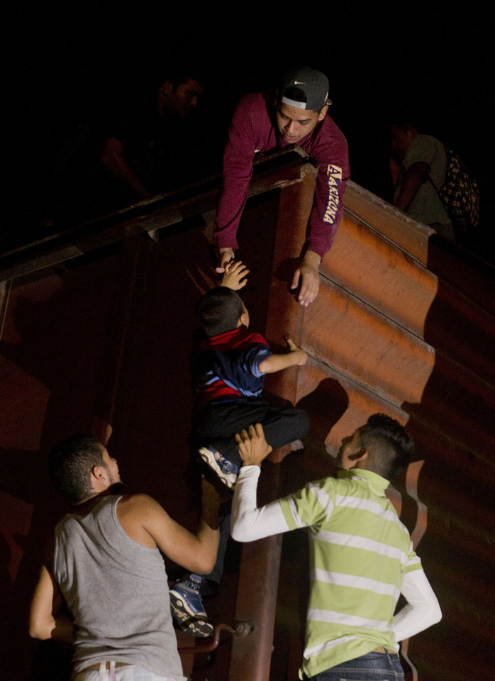 Photo - In this June 19, 2014 photo, a young boy is hoisted to the top of a boxcar, as Central Americans board a northbound freight train in Arriaga, Chiapas state, Mexico. Officials with the U.N. High Commissioner for Refugees say they hope to see a regional agreement on the Central Americans refugee status of migrants Thursday July 10, 2014, when migration and interior department representatives from the U.S., Mexico, and Central America meet in Nicaragua. The group will discuss updating a 30-year-old declaration regarding the obligations nations have to aid refugees. (AP Photo/Rebecca Blackwell)