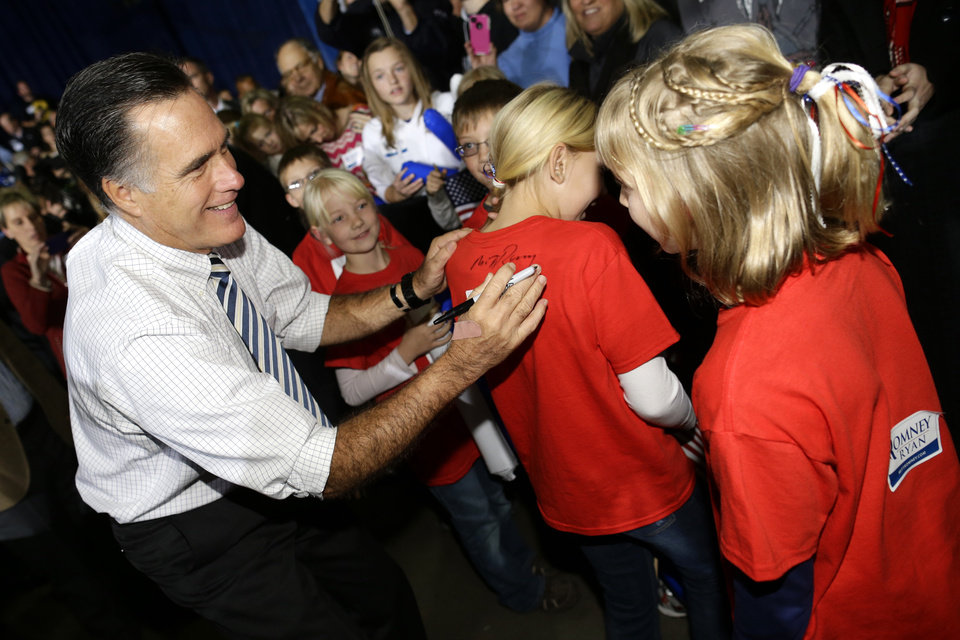 Republican presidential candidate and former Massachusetts Gov. Mitt Romney signs shirts for children as he campaigns at the Iowa Events Center, in Des Moines, Sunday, Nov. 4, 2012. (AP Photo/Charles Dharapak)