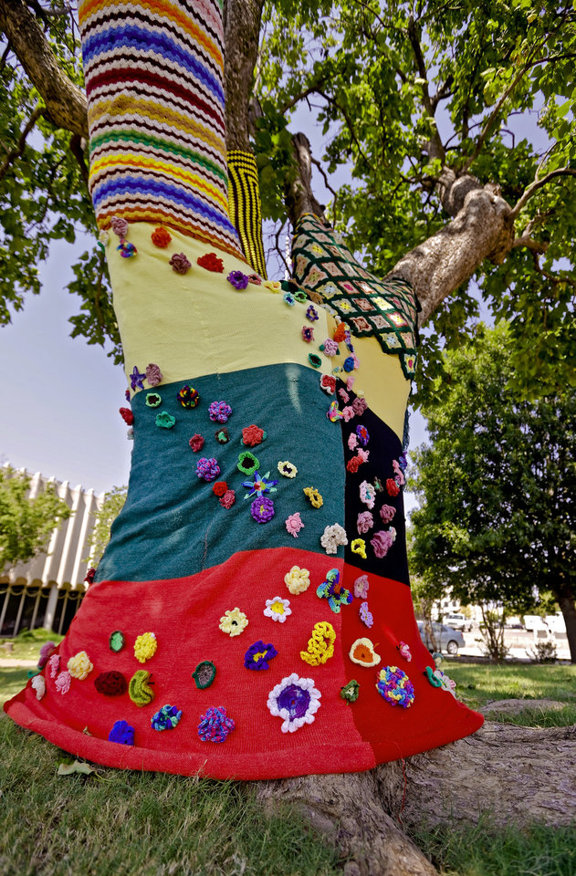 Photo - Knitted art is displayed on a tree in the Enid town square as part of the Yarnover Enid community art event on Friday, Sept. 6, 2013 in Enid, Okla. The public art project was established to bring the town together to display 'art graffiti' created from items made and donated by the community.  Photo by Chris Landsberger, The Oklahoman