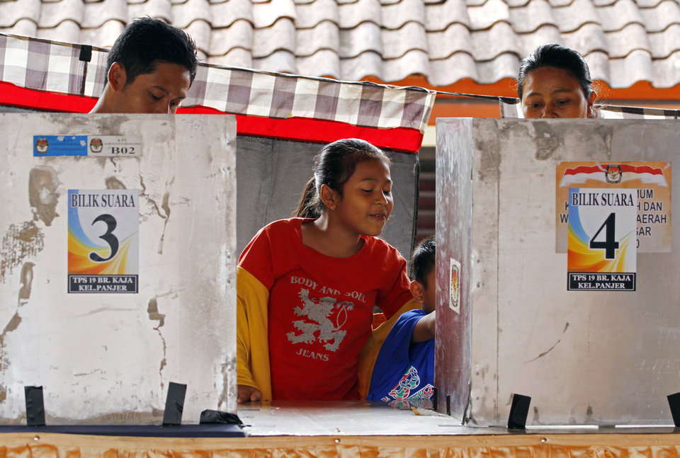 Photo - Children wait for their parents voting in the presidential election in Bali, Indonesia, Wednesday, July 9, 2014. As the world's third-largest democracy began voting Wednesday to elect a new president, Indonesians are divided between two very different choices: a one-time furniture maker, Jakarta Governor Joko Widodo, and a wealthy ex-army general with close links to former dictator Suharto, Prabowo Subianto. (AP Photo/Firdia Lisnawati)