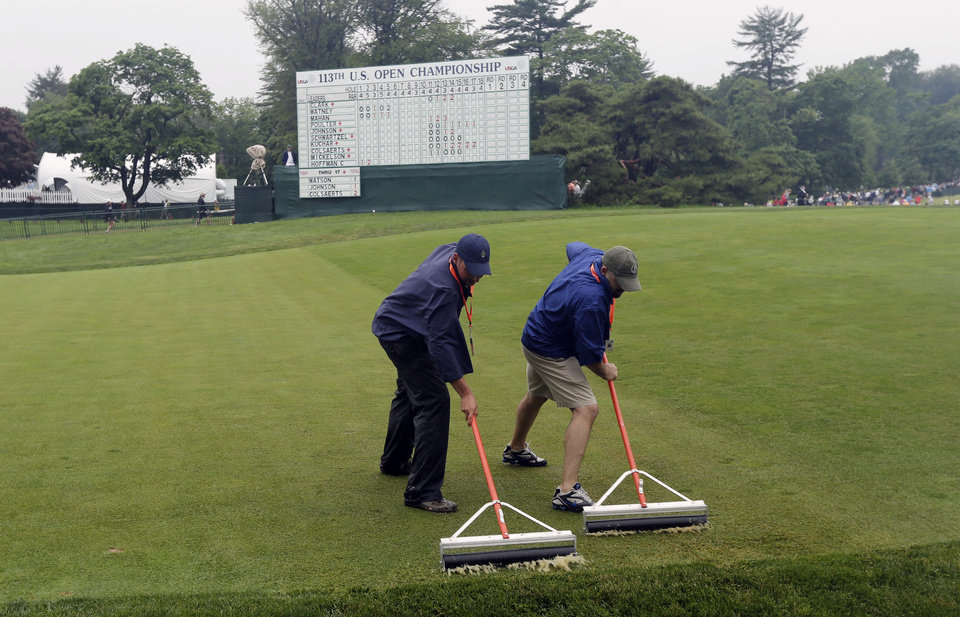 Photo - Course workers clear water from the 18th green after a weather delay during the first round of the U.S. Open golf tournament at Merion Golf Club, Thursday, June 13, 2013, in Ardmore, Pa. (AP Photo/Charlie Riedel)