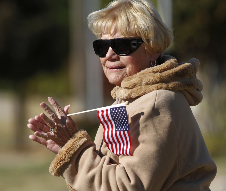 Photo - A woman claps as units in the parade pass in front of her. The city of Midwest City teamed with civic leaders and local merchants to display their appreciation for veterans and active military forces by staging a hour-long Veteran's Day parade that stretched more than a mile and a half along three of the city's busiest streets Monday morning, Nov. 12, 2012. Hundreds of people lined the parade route, many of them waving small American flags that had ben distributed by volunteers who marched near the front of the parade. A fly-over performed by F-16s from the138th Fighter Wing, Oklahoma Air National Guard unit in Tulsa thrilled spectators. Five veterans representing military personnel who served in five wars and military actions served as  Grand Marshals for the parade. Leading the parade was the Naval Reserve seven-story American flag, carried by 100 volunteers from First National Bank of Midwest City, Advantage Bank and the Tinker Federal Credit Union. The flag is 50 feet by 76 feet, weighs 110 pounds and was sponsored by the MWC Chapter of Disabled American Veterans. Photo by Jim Beckel, The Oklahoman