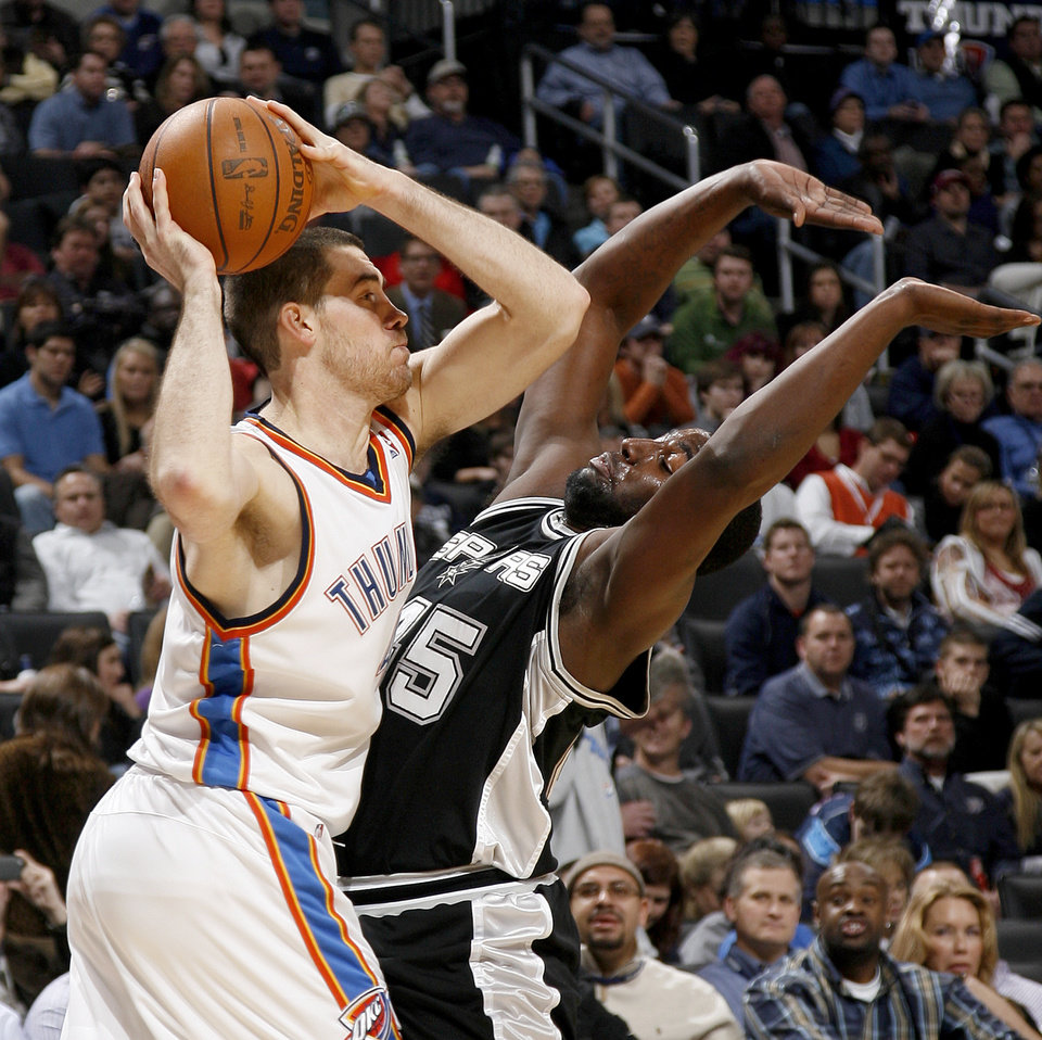 Oklahoma City's Nick Collison tries to pass around San Antonio's DeJuan Blair during the NBA basketball game between the Oklahoma City Thunder and the San Antonio Spurs at the Ford Center in Oklahoma City, Wednesday, January 13, 2010. Photo by Bryan Terry, The Oklahoman