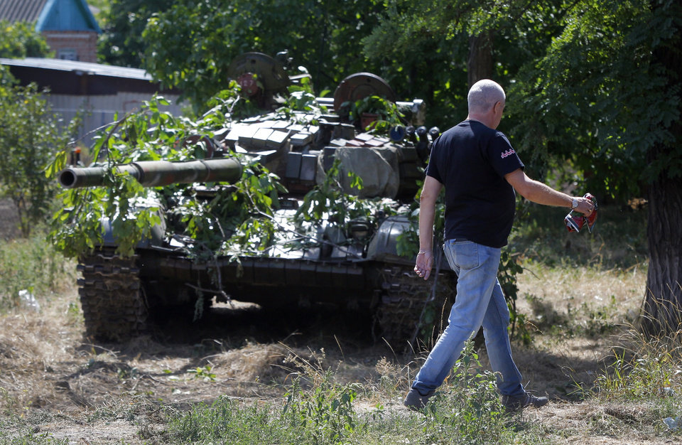 Photo - A local resident passes by camouflaged pro-Russian tank in the town of Novoazovsk, in eastern Ukraine, Friday, Aug. 29, 2014. In Novoazovsk, pro Russian rebel fighters looked to be in firm control, well-equipped and relaxed. At least half a dozen tanks were seen on roads around the town, although the total number at the rebels' disposal is believed to be much greater. Novoazovsk fell swiftly to the rebels Wednesday after being pounded by shelling.(AP Photo/Sergei Grits)