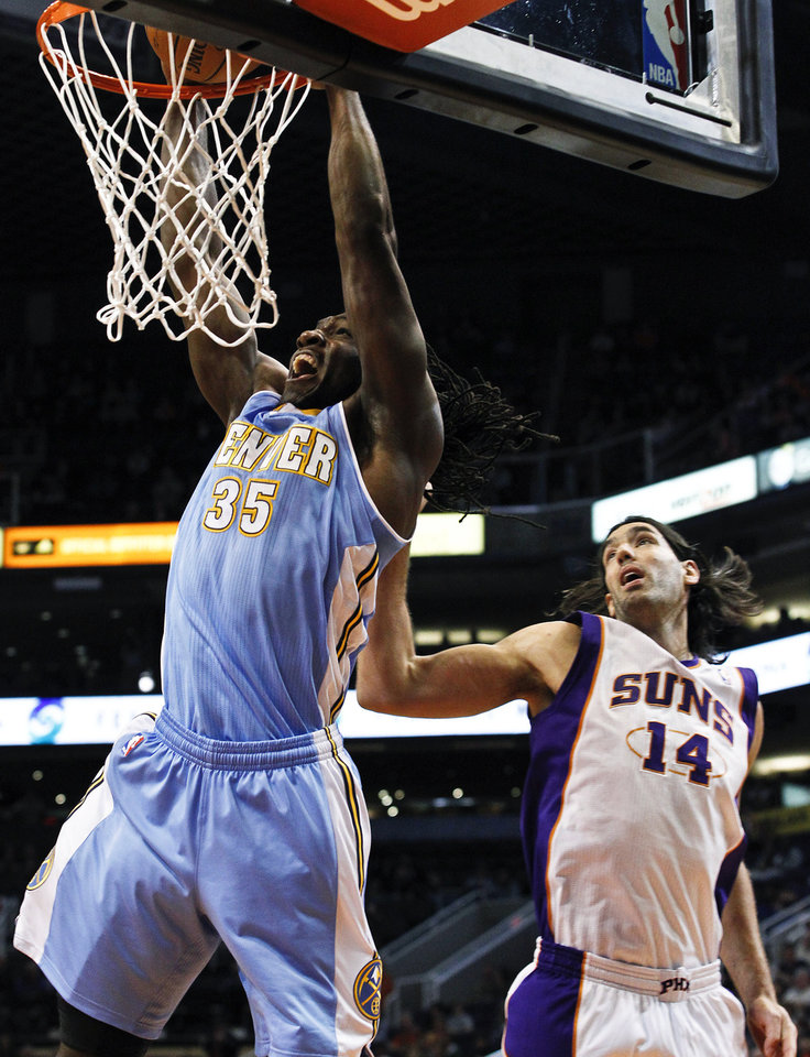 Denver Nuggets' Kenneth Faried (35) dunks past Phoenix Suns' Luis Scola (14), of Argentina, in the first half of an NBA basketball game, Monday, Nov. 12, 2012, in Phoenix. (AP Photo/Ross D. Franklin)