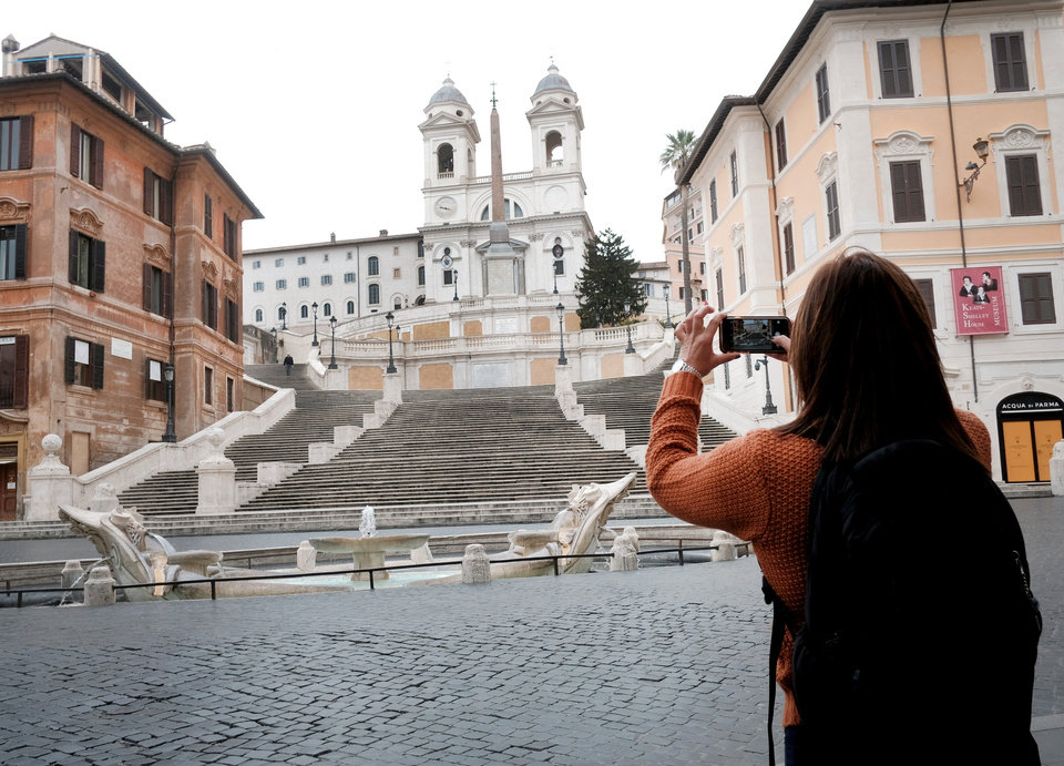 Photo -  A woman takes photos of The Spanish Steps in Rome Friday, March 13, 2020. A sweeping lockdown is in place in Italy to try to slow down the spread of coronavirus epidemic. For most people, the new coronavirus causes only mild or moderate symptoms. For some, it can cause more severe illness, especially in older adults and people with existing health problems. (Mauro Scrobogna/LaPresse via AP)