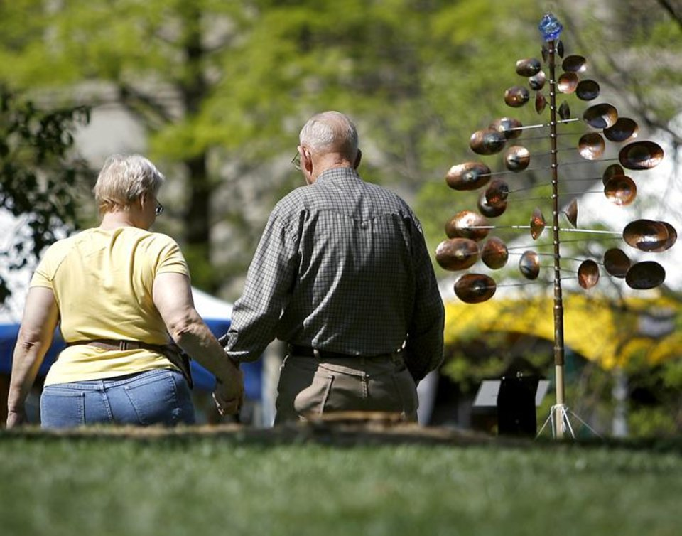 Photo -  Truman and June Garland, of Moore, hold hands as they walk past artwork during the Festival of the Arts in downtown Oklahoma City on Wednesday, April 22, 2009. Photo by John Clanton, The Oklahoman ORG XMIT: KOD