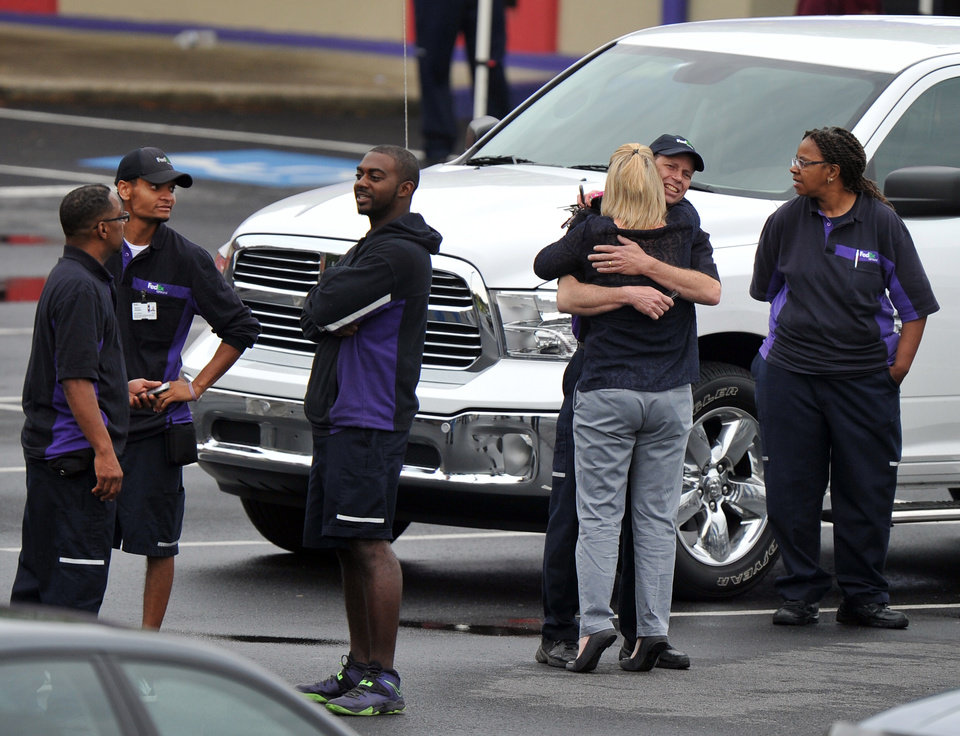 Photo - FedEx Employees and family members gather a skating rink following a shooting at the FedEx facility in Kennesaw, Ga., on Tuesday, April 29, 2014.  A shooter described as being armed with an assault rifle and having bullets strapped across his chest