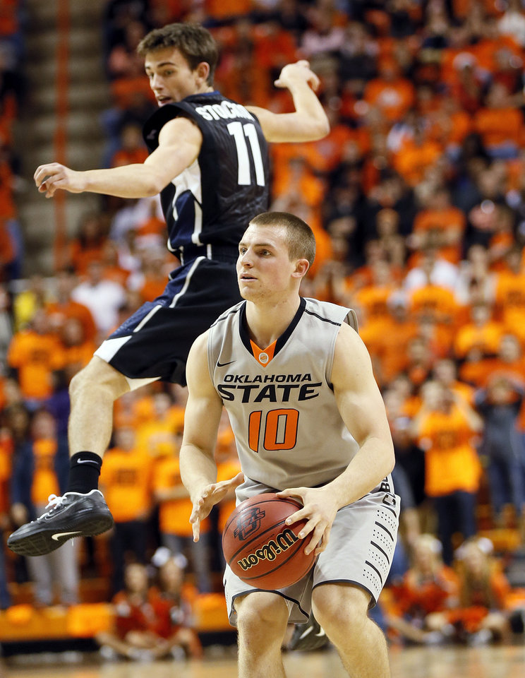 Photo - Oklahoma State's Phil Forte (10) looks to shoot after avoiding Gonzaga's David Stockton (11) during a men's college basketball game between Oklahoma State University (OSU) and Gonzaga at Gallagher-Iba Arena in Stillwater, Okla., Monday, Dec. 31, 2012. Photo by Nate Billings, The Oklahoman