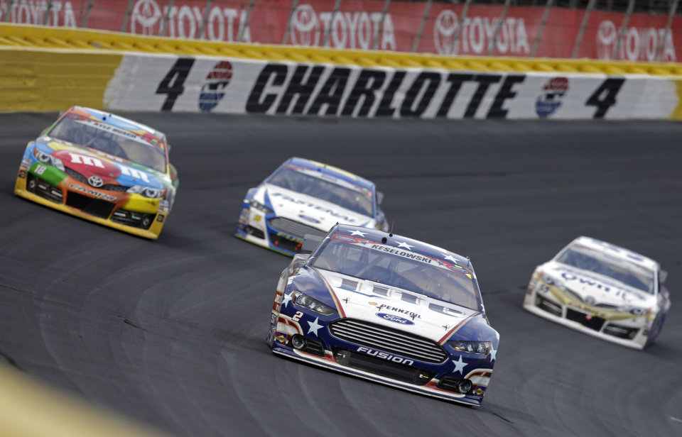 Photo - Driver Brad Keselowski (2) leads a pack of cars through Turn 4 during the NASCAR Sprint Cup series Coca-Cola 600 auto race at Charlotte Motor Speedway in Concord, N.C., Sunday, May 25, 2014. (AP Photo/Chuck Burton)