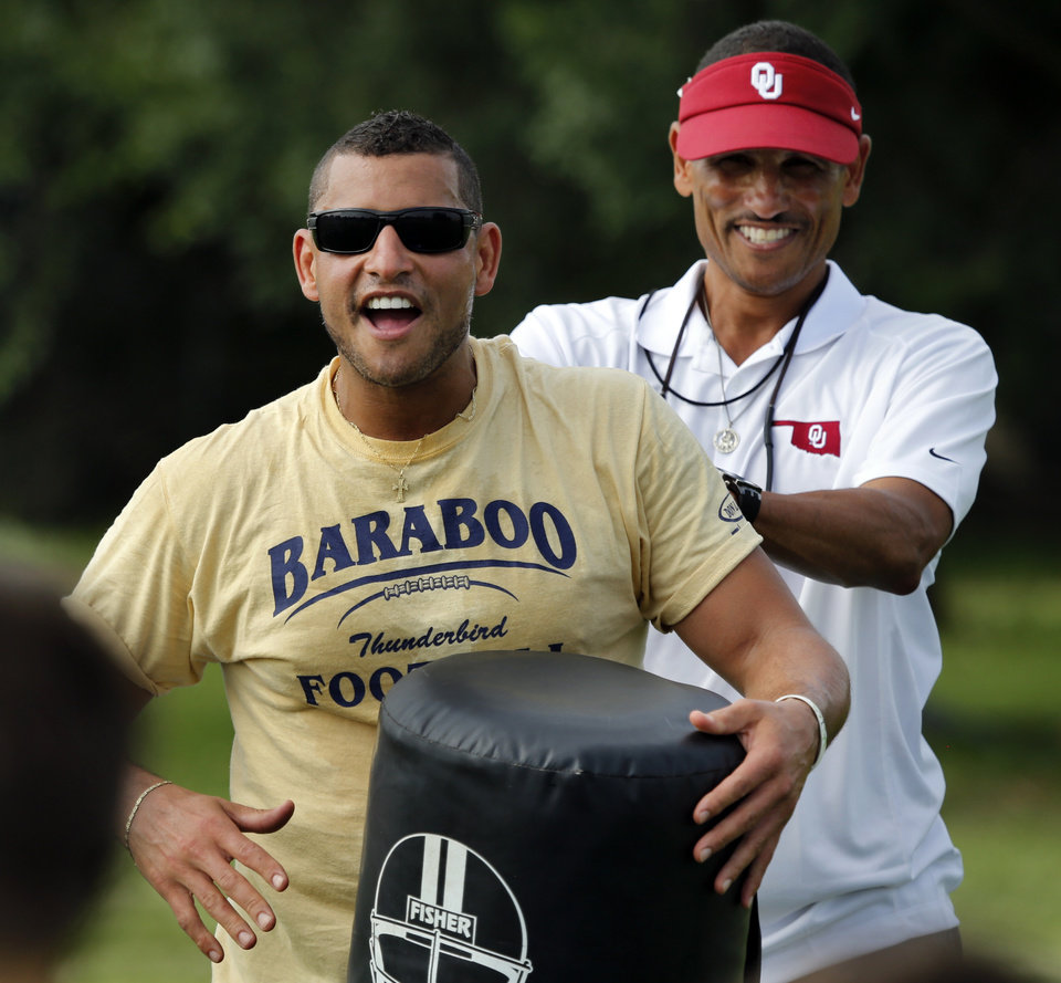 Photo - University of Oklahoma's (OU) co-offensive coordinator Jay Norvell, right, gets his brother Aaron Norvell involves as he hosts his annual youth camp at Whittier Middle School on Tuesday, June 17, 2014 in Norman, Okla.  Photo by Steve Sisney, The Oklahoman