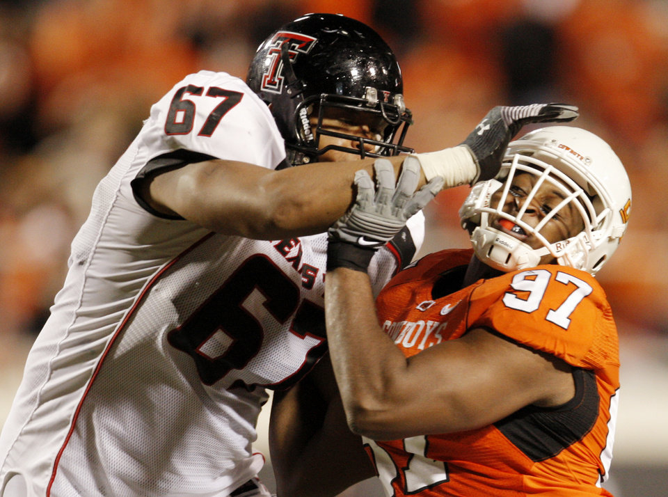 Photo - Cowboy Jermiah Price (97) fights off the block of Marlon Winn (67) during the college football game between Oklahoma State University (OSU) and Texas Tech University at Boone Pickens Stadium in Stillwater, Okla. Saturday, Nov. 14, 2009. Photo by Doug Hoke, The Oklahoman