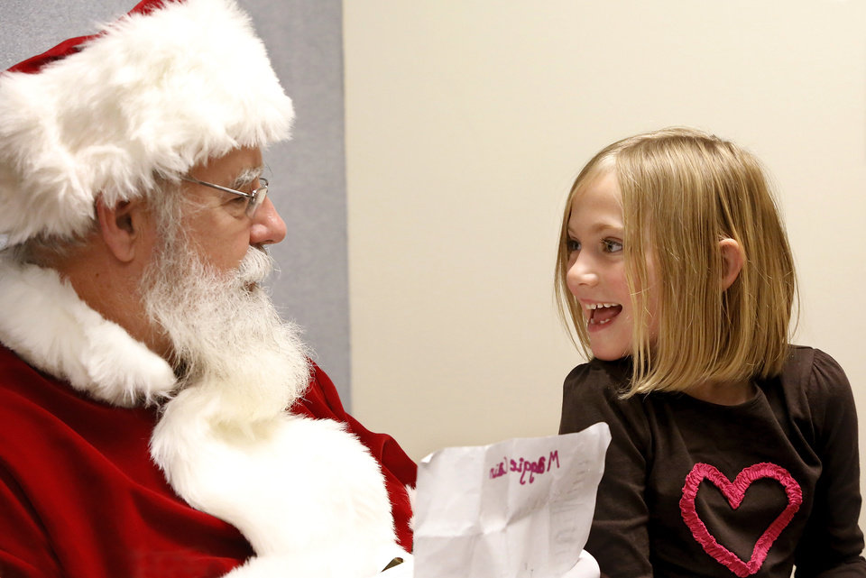 Santa stopped by the Edmond police station Saturday, Dec. 22, 2012, to visit with children, hear their Christmas lists and pose for keepsake photos that were provided for the children by Edmond police department.  Smiling back  at Santa when he asks about an item on her wish list is Maggie Cain, 6.   Playing Santa is Boyd Mize, a retired detective with the Edmond police department.  This is the eighth year Mize has donned the Santa suit for the police department's day with Santa.  But Mize said this is the first year he didn't have to wear a fake beard; all the hair on Santa's face is natural this year. Photo by Jim Beckel, The Oklahoman