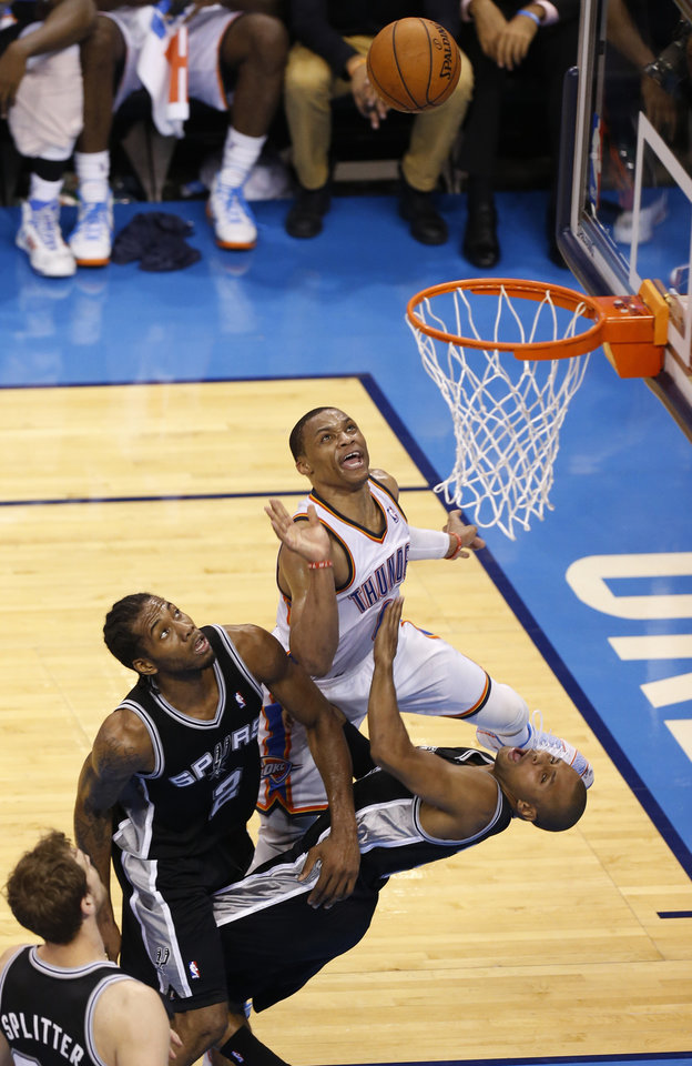 Photo - Oklahoma City's Russell Westbrook (0) drives to the basket as San Antonio's Patty Mills (8) and San Antonio's Kawhi Leonard (2) defend during Game 6 of the Western Conference Finals in the NBA playoffs between the Oklahoma City Thunder and the San Antonio Spurs at Chesapeake Energy Arena in Oklahoma City, Saturday, May 31, 2014. Photo by Nate Billings, The Oklahoman