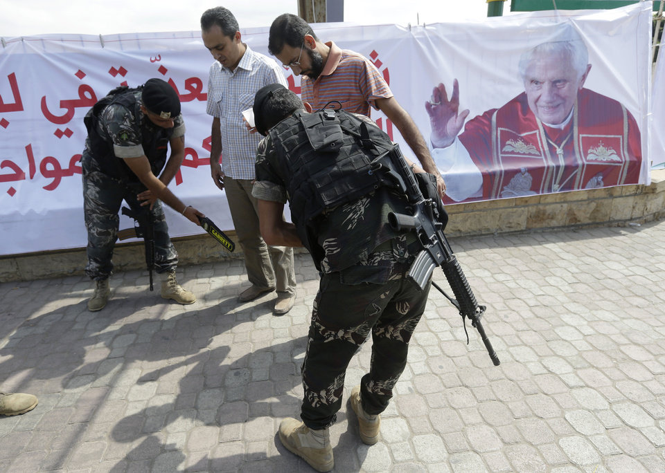 Photo -   Lebanese Army soldiers search citizens outside Rafik Hariri international airport during a security measure, in Beirut, Lebanon, Friday Sept. 14, 2012. Pope Benedict XVI is expected to arrive in Lebanon for a three day visit to encourage his flock in the Middle East. He will also meet with Lebanese authorities as well as Christians from Lebanon and other nearby countries.(AP Photo/Hussein Malla)