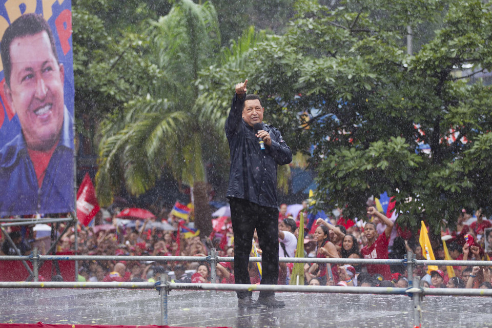 Under pouring rain, Venezuela's President Hugo Chavez gestures to supporters during his closing campaign rally in Caracas, Venezuela, Thursday, Oct. 4, 2012. Chavez is running for re-election against opposition candidate Henrique Capriles in presidential elections on Oct . 7. (AP Photo/Ariana Cubillos)