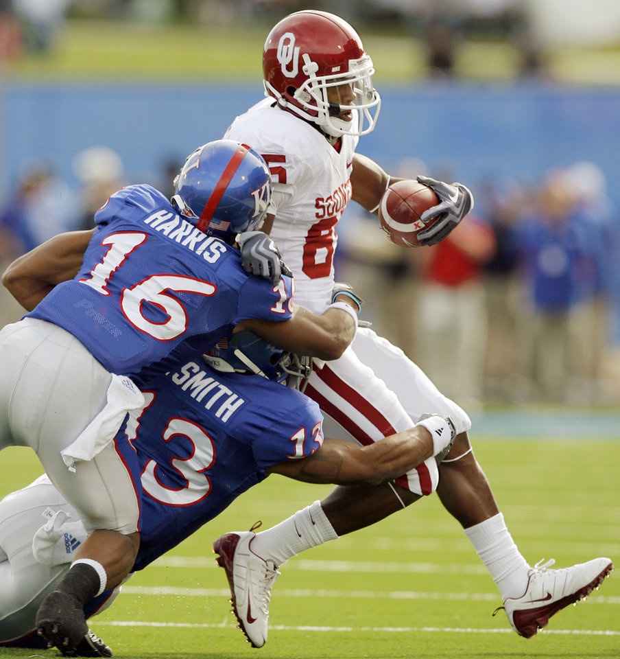 Photo - KU's Chris Harris (16) and Lubbock Smith (13) tackle OU's Ryan Broyles (85) after a catch during the first half of the college football game between the University of Oklahoma Sooners (OU) and the University of Kansas Jayhawks (KU) on Saturday, Oct. 24, 2009, in Lawrence, Kan. OU won, 35-13. Photo by Nate Billings, The Oklahoman
