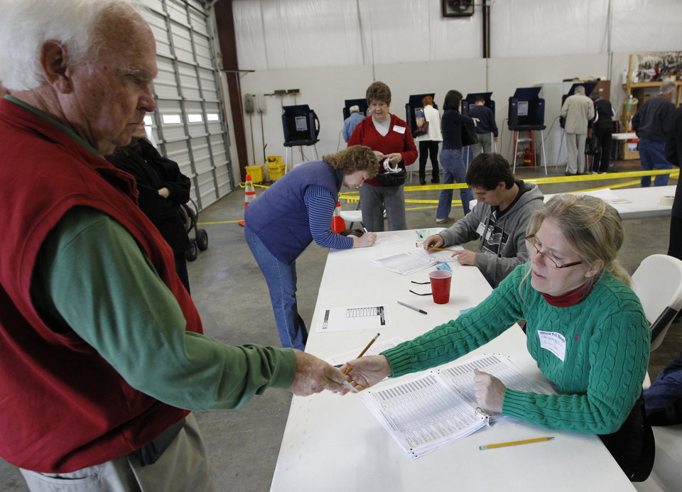 Photo - Poll manager Marguerite McClam, right, checks voter identification as South Carolinians arrive to vote in the Republican presidential primary at the Amicks Ferry Fire Station in Chapin, S.C., Saturday, Jan., 21, 2012. (AP Photo/Pablo Martinez Monsivais) ORG XMIT: SCPM106
