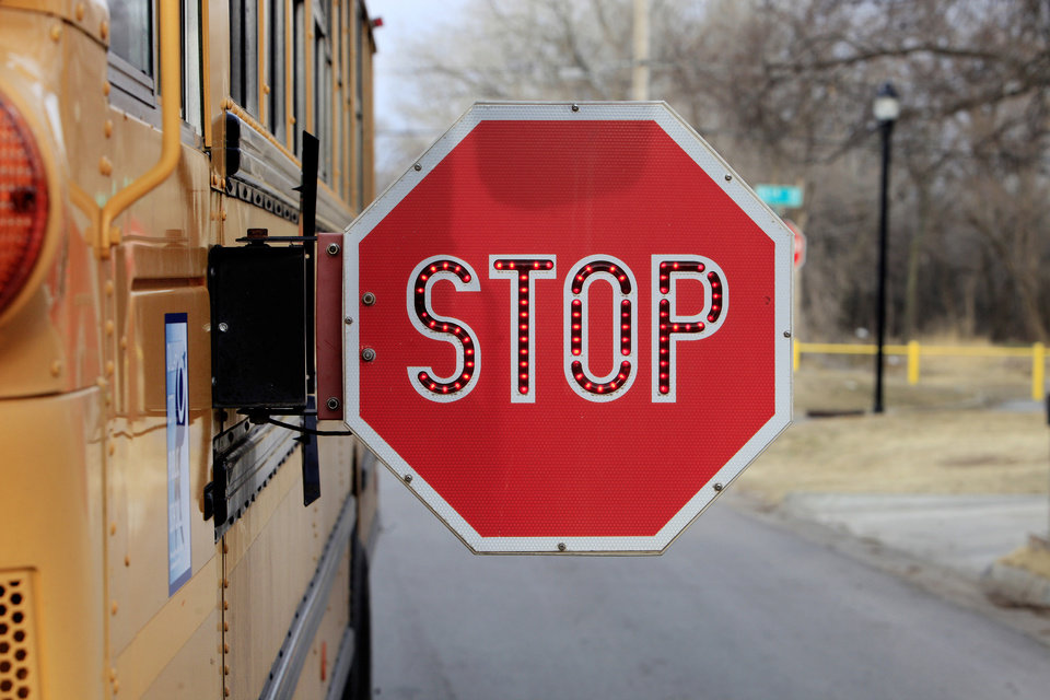 Photo - An Oklahoma City Public School bus has its stop sign out and flashing as it picks up a student at NW 3 Street and Villa in Oklahoma City on March 7.  Photo by Paul B. Southerland, The Oklahoman  PAUL B. SOUTHERLAND - PAUL B. SOUTHERLAND