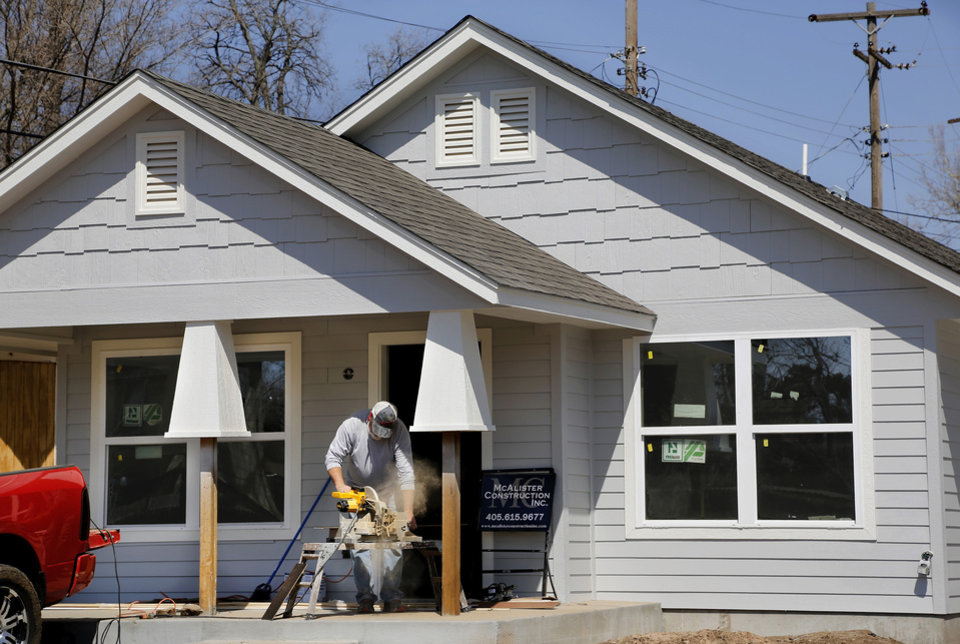 Photo - A worker makes repairs on a Positively Paseo house under renovation at 1511 NW 14.  Jim Beckel -